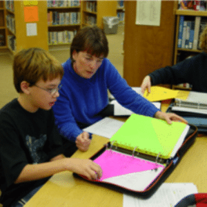 Photo Anne Blumer working with middle school students to organize their assignments and binders